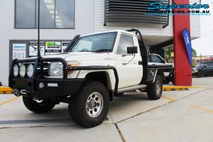 """Front right view of a white single cab 79 Series Toyota Landcruiser before fitting a 4"""" inch Superior Remote Reservoir Superflex Kit + Tru Tracker Kit"""
