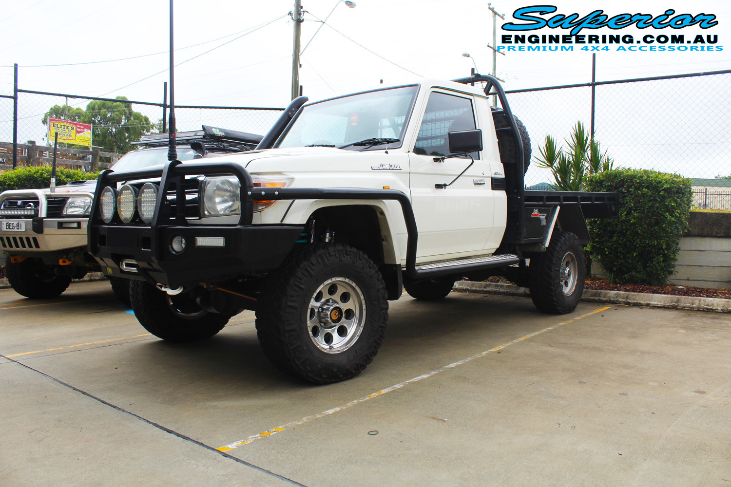 "Front right view of a white single cab 79 Series Toyota Landcruiser after fitting a 4"" inch Superior Remote Reservoir Superflex Kit + Tru Tracker Kit"