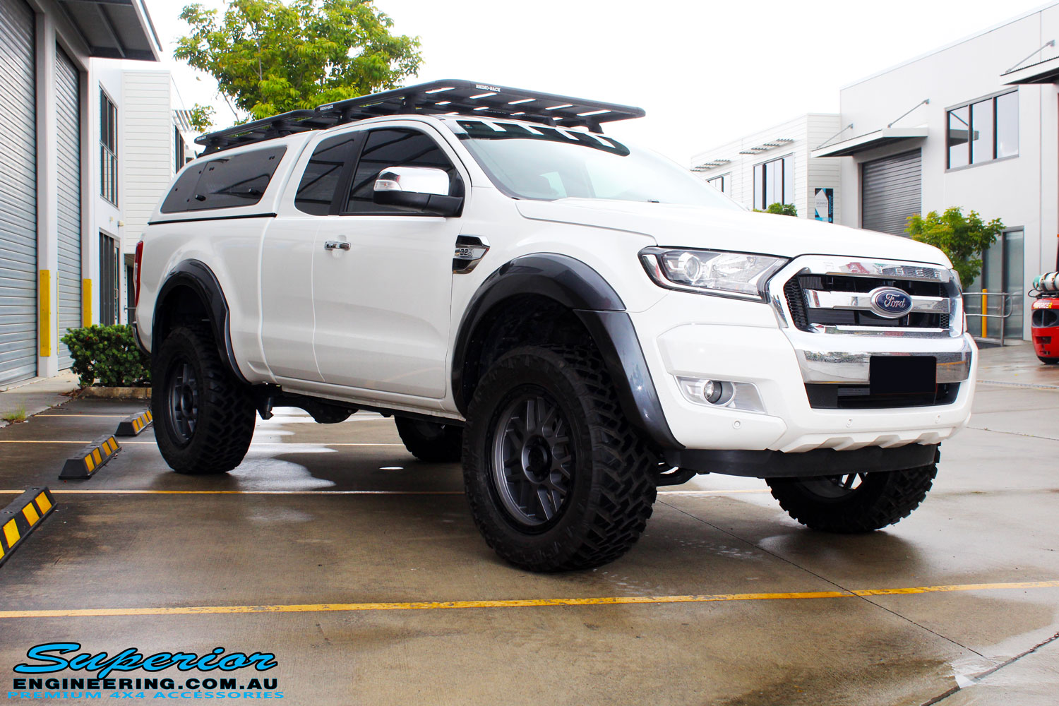 Right front side view of a White Ford PXII Ranger after fitment of the Superior Diff Drop Kit