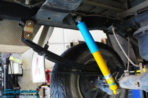"""Rear left underbody view of a fitted Bilstein 2"""" Rear Shock with Leaf Springs"""