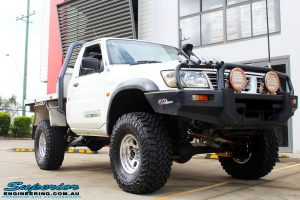 """Right front side view of a White GU Patrol Ute after fitment of a Superior Nitro Gas Hyperflex 4"""" Inch Lift Kit, Tie Rod Heim Joint + Coil Tower Brace Kit"""