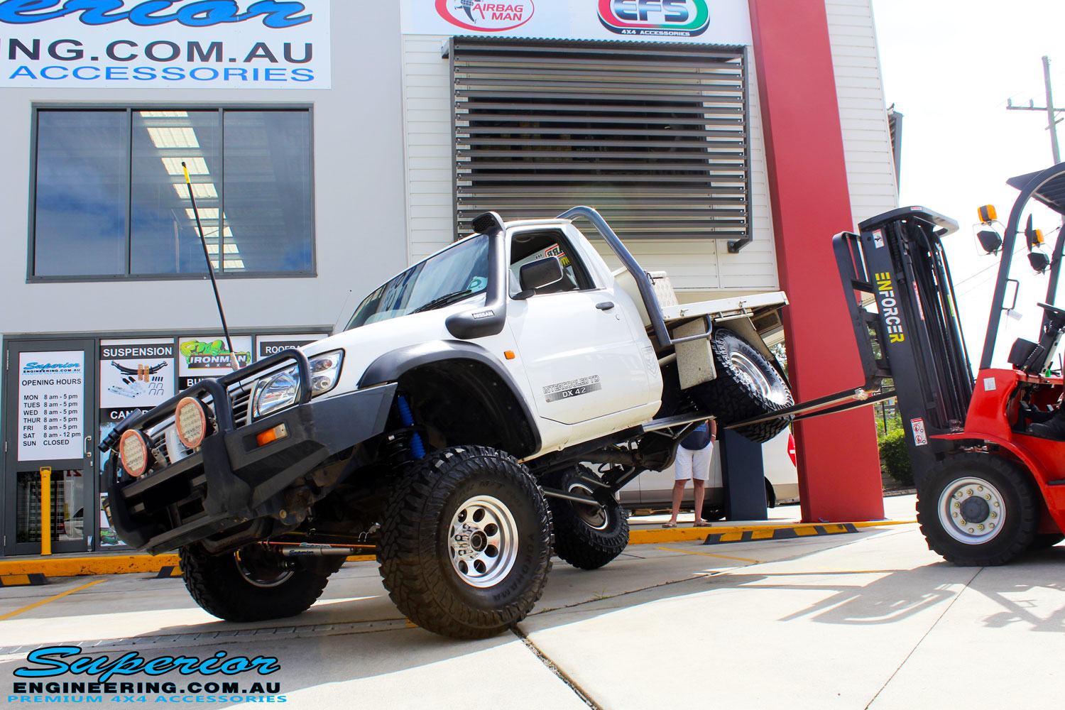 """Left front side view of a White GU Patrol Ute showing its flex after fitment of a Superior Nitro Gas Hyperflex 4"""" Inch Lift Kit, Tie Rod Heim Joint + Coil Tower Brace Kit"""