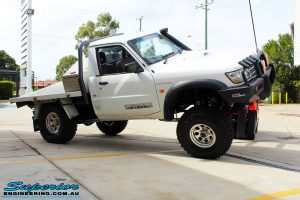"""Right front side view of a White GU Patrol Ute showing its flex after fitment of a Superior Nitro Gas Hyperflex 4"""" Inch Lift Kit, Tie Rod Heim Joint + Coil Tower Brace Kit"""