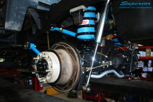 Rear view of the left hub assembly after fitment showing Remote Reservoir Shock, Coil Spring with Airbag Man Coil Helper and Lower & Upper Control Arms.
