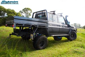 """Rear right side view whilst flexing of a Grey Toyota 79 Series Landcruiser Dual Cab after fitment of a Superior 4"""" Inch Rear Coil Conversion Kit with Hyperflex Radius Arms, Remote Reservoir Shocks and a Airbag Man 4"""" Inch Coil Helper Air Kit."""