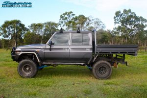 """Left side view of a Grey Toyota 79 Series Landcruiser Dual Cab after fitment of a Superior 4"""" Inch Rear Coil Conversion Kit with Hyperflex Radius Arms, Remote Reservoir Shocks and a Airbag Man 4"""" Inch Coil Helper Air Kit."""