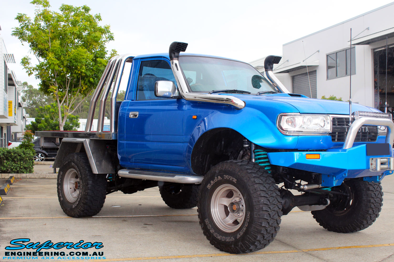 """Left front side view of a Blue Toyota 80 Series Landcruiser Ute Chop after fitment of a Airbag Man 4"""" Inch Coil Air Lift Kit"""