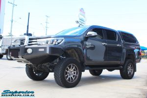 "Left front side view of a Grey Toyota Hilux Revo Dual Cab after fitment of a Superior Remote Reservoir 4"" Inch Lift Kit"