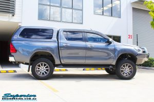 """Side view of a Grey Toyota Hilux Revo Dual Cab after fitment of a Superior Remote Reservoir 4"""" Inch Lift Kit"""