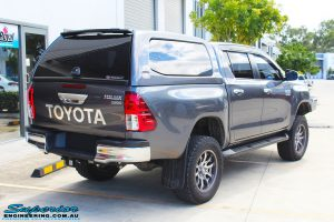 """Rear right view of a Grey Toyota Hilux Revo Dual Cab after fitment of a Superior Remote Reservoir 4"""" Inch Lift Kit"""