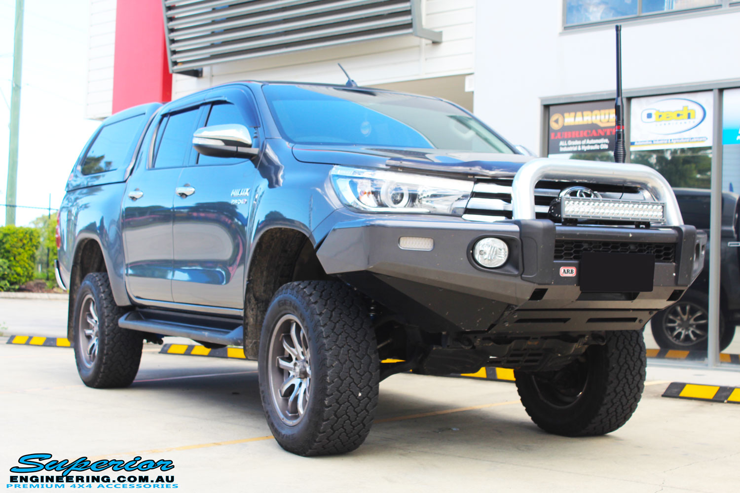 "Right front side view of a Grey Toyota Hilux Revo Dual Cab after fitment of a Superior Remote Reservoir 4"" Inch Lift Kit"