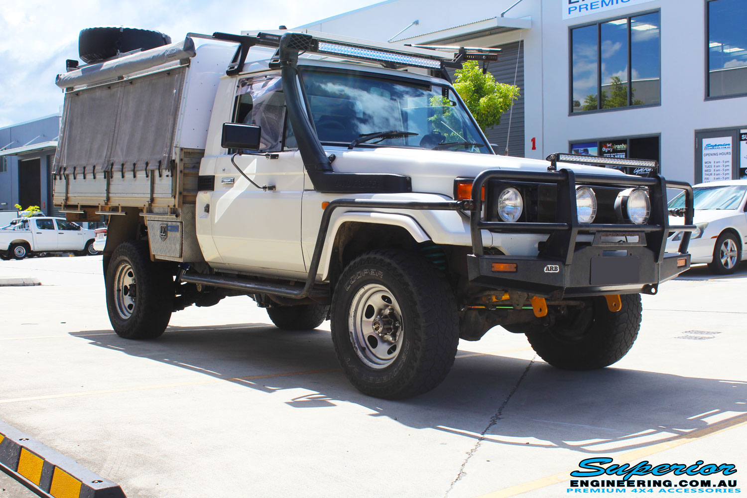 """Right front side view of a White Toyota Landcruiser 79 Series after fitment of a Superior Nitro Gas 2"""" Inch Lift Kit"""