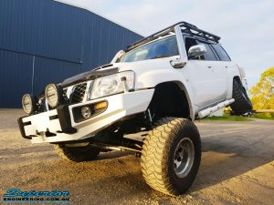 Left front side view of a White Nissan GU Patrol Wagon flexing after the fitment of a range of high quality Superior Engineering 4x4 Suspension & Accessories