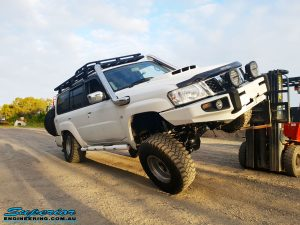 Right front view of a White Nissan GU Patrol Wagon flexing its front left wheel after the fitment of a range of high quality Superior Engineering 4x4 Suspension & Accessories