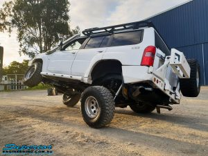 Left rear view of a White Nissan GU Patrol Wagon flexing its front left wheel after the fitment of a range of high quality Superior Engineering 4x4 Suspension & Accessories