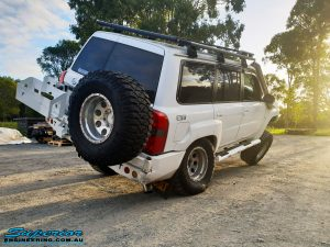 Right rear view of a White Nissan GU Patrol Wagon flexing its front left wheel after the fitment of a range of high quality Superior Engineering 4x4 Suspension & Accessories