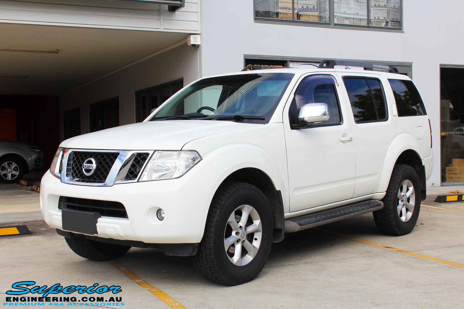 Left front side view of a White Nissan R51 Pathfinder Wagon after fitment of a Tough Dog 40mm Lift Kit