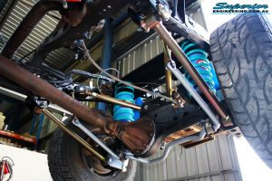 "Left underbody rear view looking up on the fitted Superior Lower Control Arms, 2"" Inch Nitro Gas Shock Absorbers, Coil Springs with Airbag Man Coil Air Kit and Sway Bar Kit"