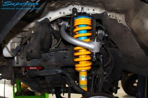 "Front left inside guard view of the fitted Bilstein 4"" Strut + Superior Coil Spring, Upper Control Arm & Sway Bar Relocation Plate"