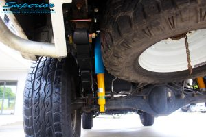 "Rear left underbody shot of the fitted Bilstein 4"" Shock with EFS Leaf Springs and U-Bolt Kit"
