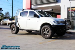 Right front side view of a White Mitsubishi MN Triton before fitment of a 20mm Lift Kit