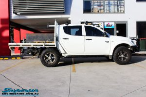 Side view of a White Mitsubishi MN Triton before fitment of a 20mm Lift Kit