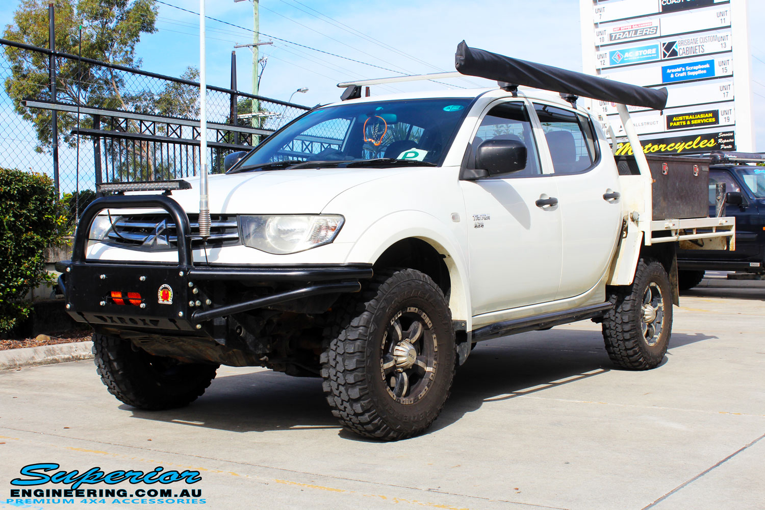 Left front side view of a White Mitsubishi MN Triton after fitment of a 20mm Lift Kit