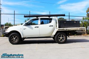Side view of a White Mitsubishi MN Triton after fitment of a 20mm Lift Kit