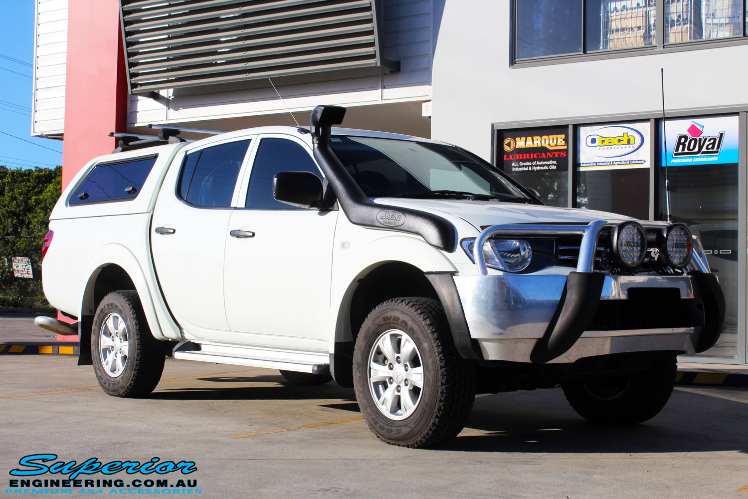 Right front side view of a Mitsubishi MN Triton in White On The Hoist @ Superior Engineering Deception Bay Showroom