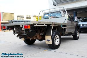 Rear right view of a Nissan GU Patrol Ute in Gold On The Hoist @ Superior Engineering Deception Bay Showroom
