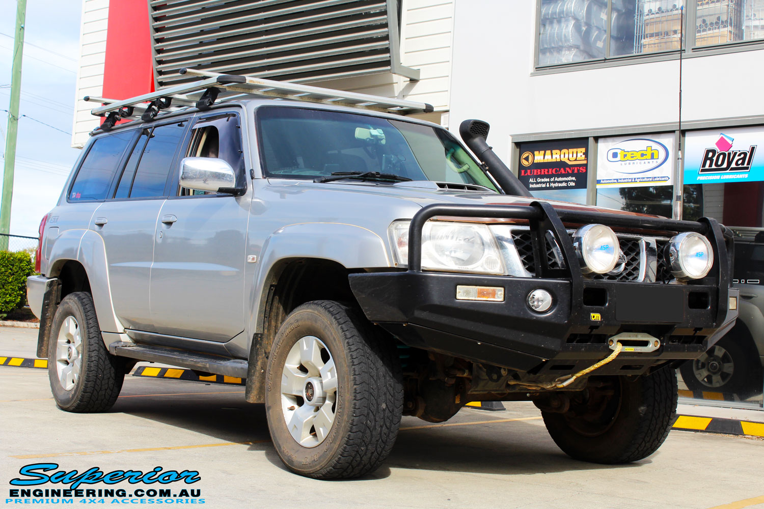 "Right front side view of a Silver Nissan GU Patrol Wagon after fitting a Dobinson 2"" Inch Lift Kit + Coil Tower Brace Kit"