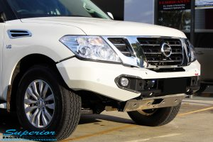 Close up front right side view of the Nissan Y62 and its fitted Rhino 4x4 Evolution 3D Winch Bar + VRS Winch
