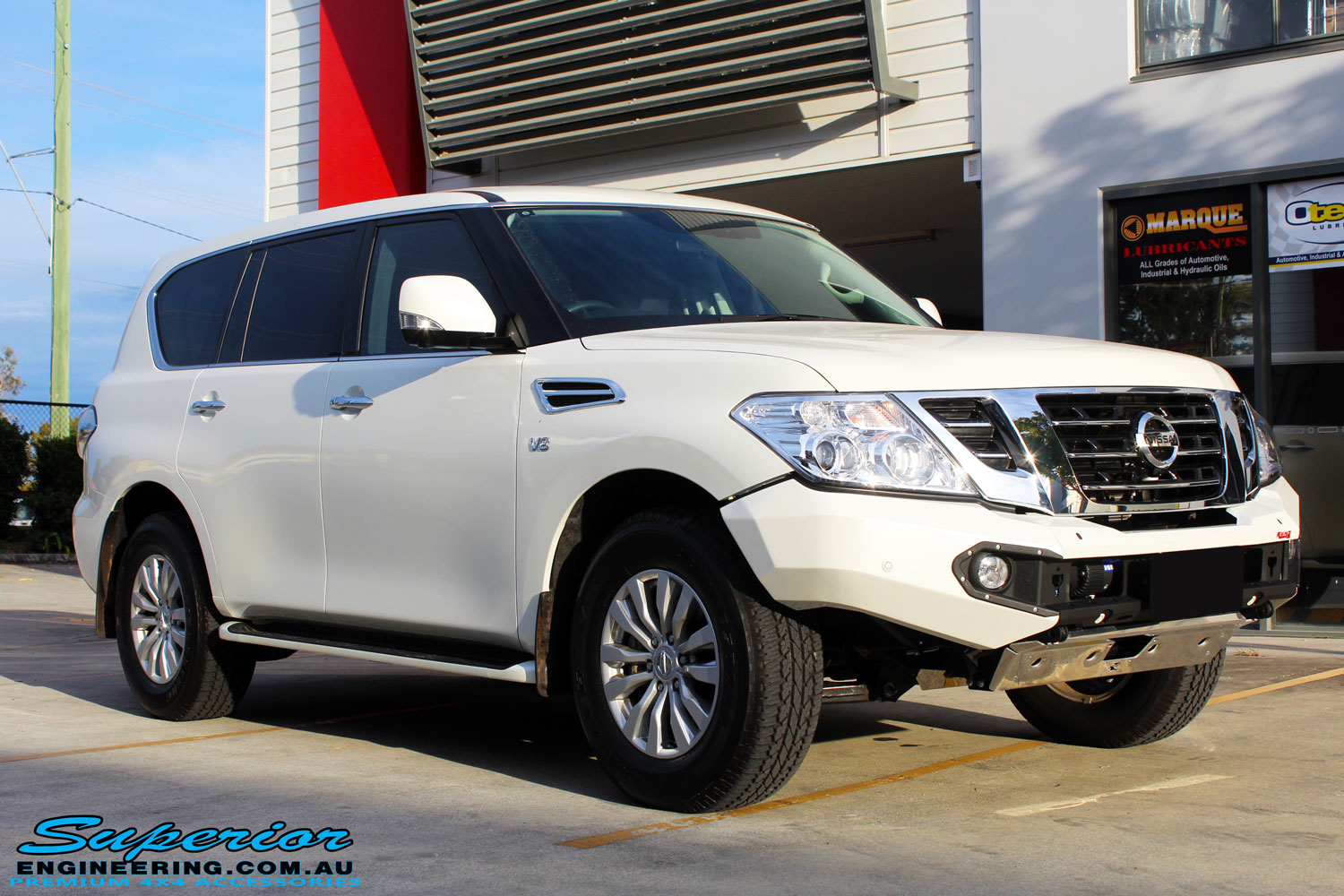 Right front side view of a White Nissan Y62 Patrol Wagon after fitment of a Rhino 4x4 Evolution 3D Winch Bar + VRS Winch