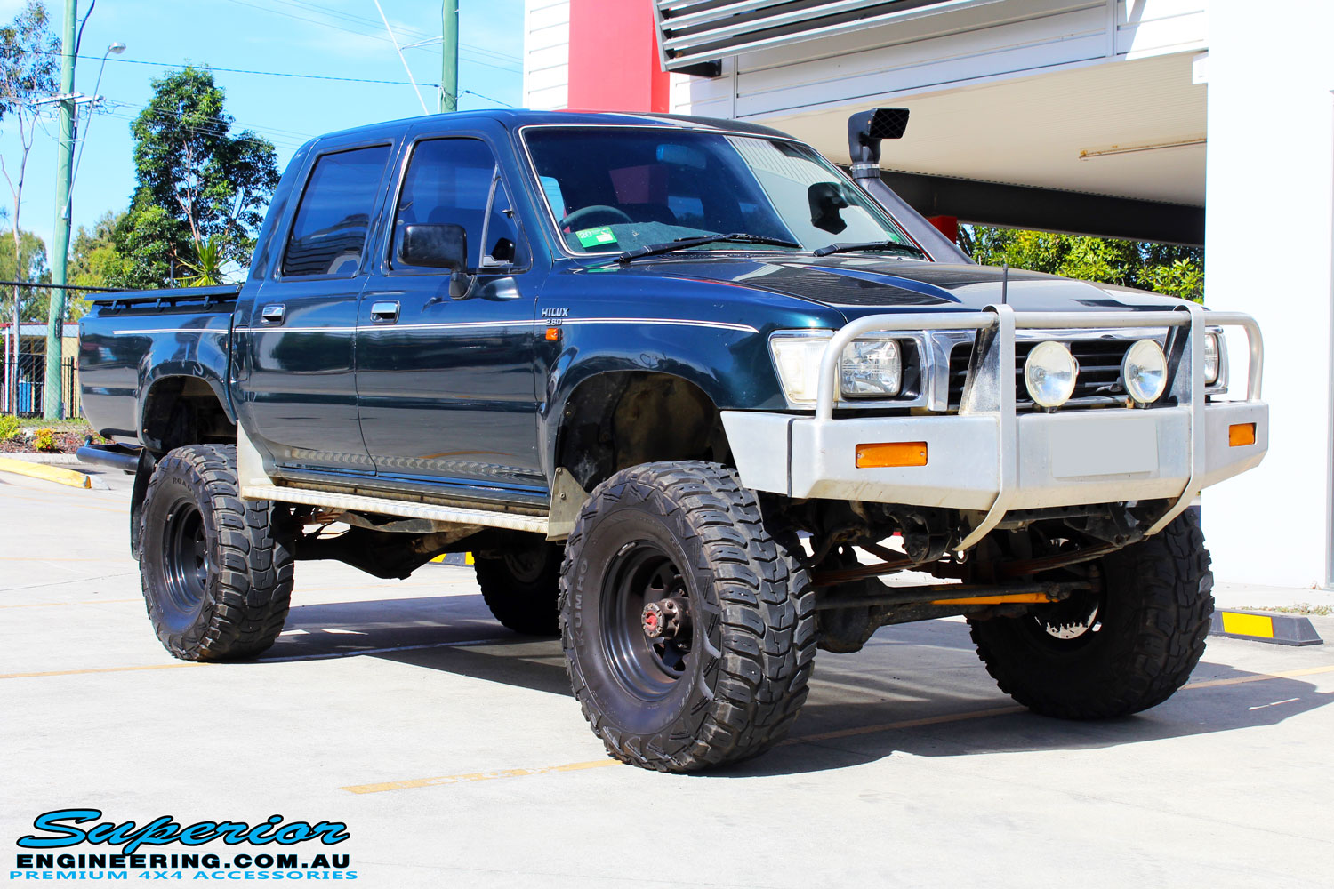 """Right front side view of a Green Toyota SAF Hilux Dual Cab before fitment of a EFS 3"""" Inch Leaf Springs Rear Lift Kit"""