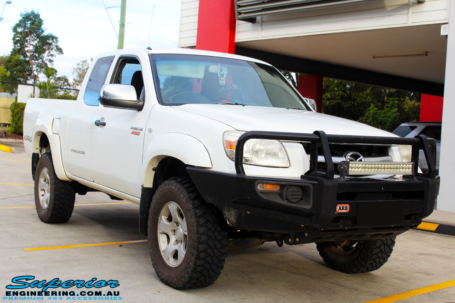 Right front side view of a White Mazda BT50 after fitment of a Bilstein 35mm Lift Kit