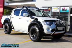 "Right front side view of a Mitsubishi ML Triton in White before fitment of a Superior Nitro Gas 2"" Inch Lift Kit"