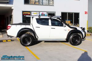 """Right side view of a Mitsubishi ML Triton in White before fitment of a Superior Nitro Gas 2"""" Inch Lift Kit"""
