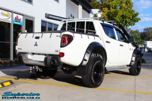 """Rear right view of a Mitsubishi ML Triton in White before fitment of a Superior Nitro Gas 2"""" Inch Lift Kit"""
