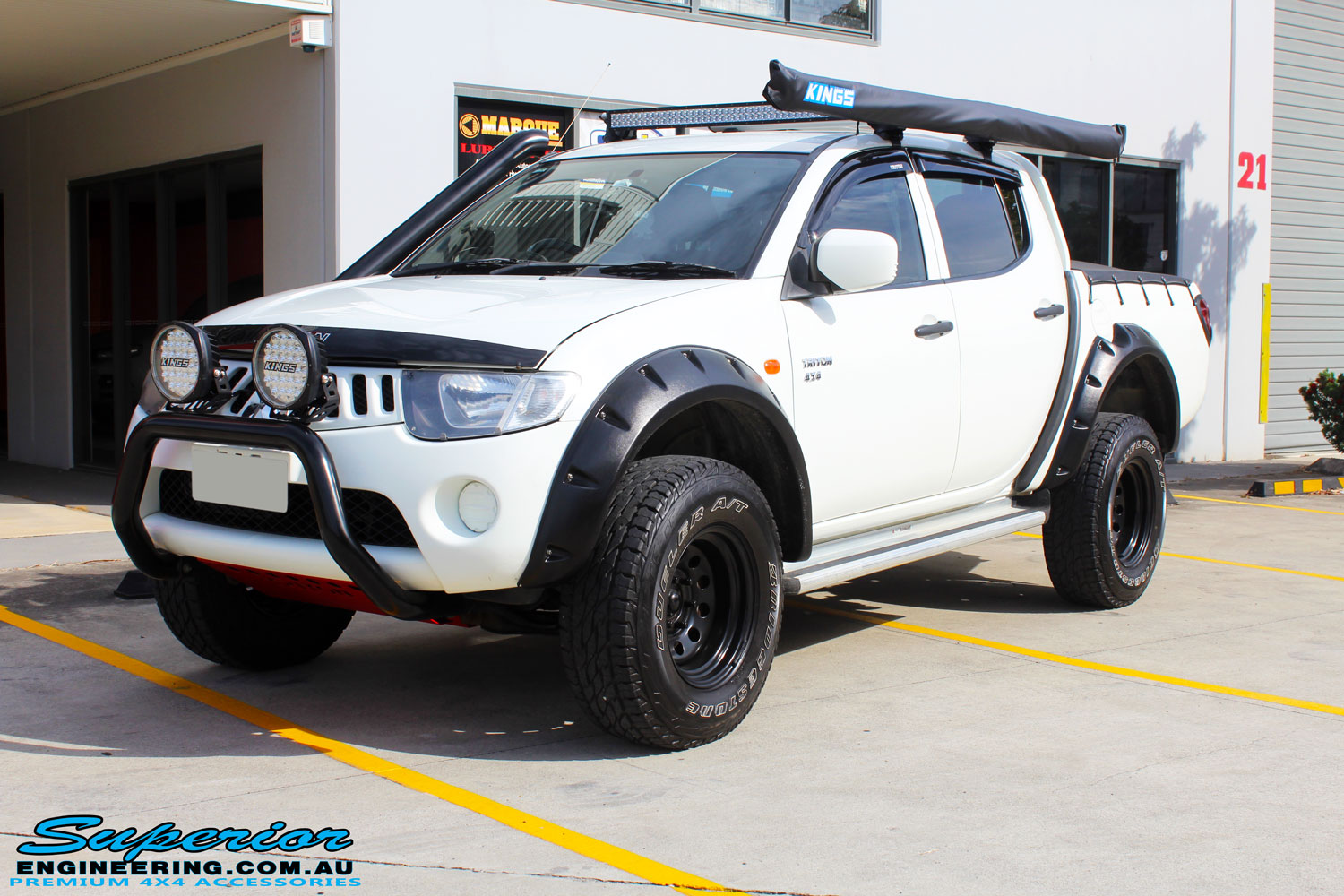 "Left front side view of a Mitsubishi ML Triton in White after fitment of a Superior Nitro Gas 2"" Inch Lift Kit"
