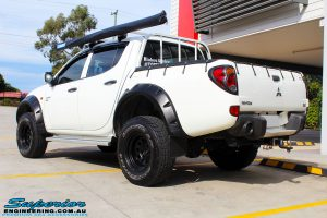 "Rear left view of a Mitsubishi ML Triton in White after fitment of a Superior Nitro Gas 2"" Inch Lift Kit"