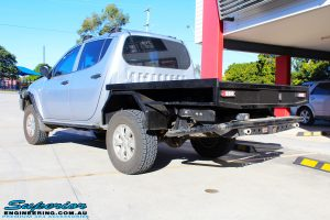 Rear left view of a Mitsubishi MN Triton in White On The Hoist @ Superior being fitted with a Chassis Brace/Repair Plate