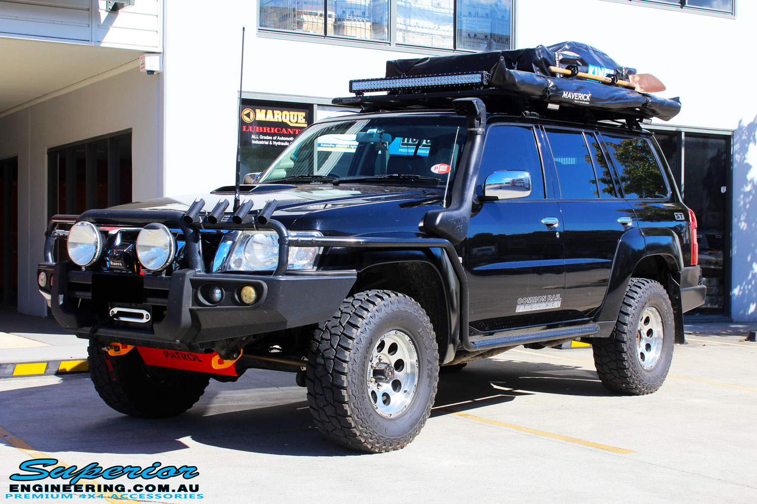 Left front side view of a Nissan GU Patrol Wagon in Black On The Hoist @ Superior Engineering Deception Bay Showroom