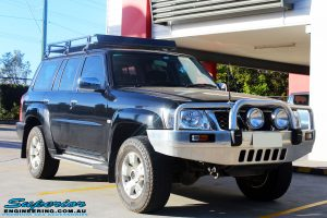 "Right front side view of a Black Nissan GU Patrol Wagon being fitted with a Superior 2"" Inch Nitro Gas Lift Kit, Airbag Man 2"" Inch Coil Air Helper Kit, Safari Snorkel, Brown Davis Long Range Fuel Tank, Superior Coil Tower Brace Kit & Superior Upper Control Arms"