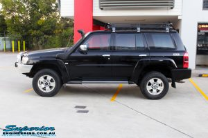 """Left side view of a Black Nissan GU Patrol Wagon after being fitted with a Superior 2"""" Inch Nitro Gas Lift Kit, Airbag Man 2"""" Inch Coil Air Helper Kit, Safari Snorkel, Brown Davis Long Range Fuel Tank, Superior Coil Tower Brace Kit & Superior Upper Control Arms"""
