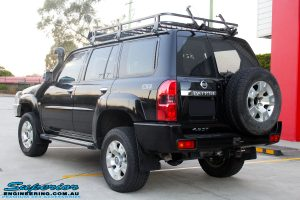 "Rear left view of a Black Nissan GU Patrol Wagon after being fitted with a Superior 2"" Inch Nitro Gas Lift Kit, Airbag Man 2"" Inch Coil Air Helper Kit, Safari Snorkel, Brown Davis Long Range Fuel Tank, Superior Coil Tower Brace Kit & Superior Upper Control Arms"