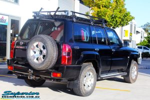 """Rear right view of a Black Nissan GU Patrol Wagon being fitted with a Superior 2"""" Inch Nitro Gas Lift Kit, Airbag Man 2"""" Inch Coil Air Helper Kit, Safari Snorkel, Brown Davis Long Range Fuel Tank, Superior Coil Tower Brace Kit & Superior Upper Control Arms"""