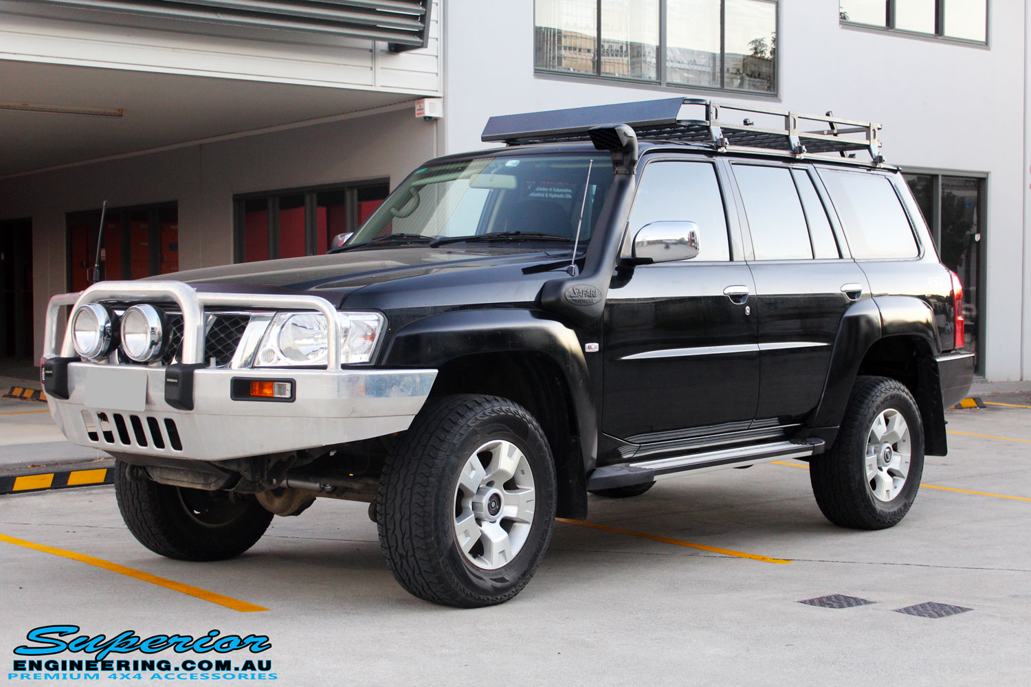 "Left front side view of a Black Nissan GU Patrol Wagon after being fitted with a Superior 2"" Inch Nitro Gas Lift Kit, Airbag Man 2"" Inch Coil Air Helper Kit, Safari Snorkel, Brown Davis Long Range Fuel Tank, Superior Coil Tower Brace Kit & Superior Upper Control Arms"