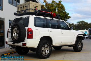 """Rear right view of a Nissan GU Patrol Wagon in White fitted with a Airbag Man Coil Air Kit 3"""" Inch Lift Kit & Superior Tie Rod Comp Spec 4340m Solid Bar whilst on the hoist at Superior"""