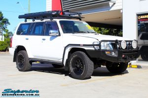 Left front side view of a Nissan GU Patrol Wagon in White On The Hoist @ Superior Engineering Deception Bay Showroom