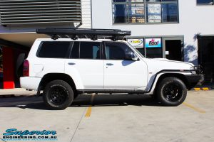 Left side view of a Nissan GU Patrol Wagon in White On The Hoist @ Superior Engineering Deception Bay Showroom